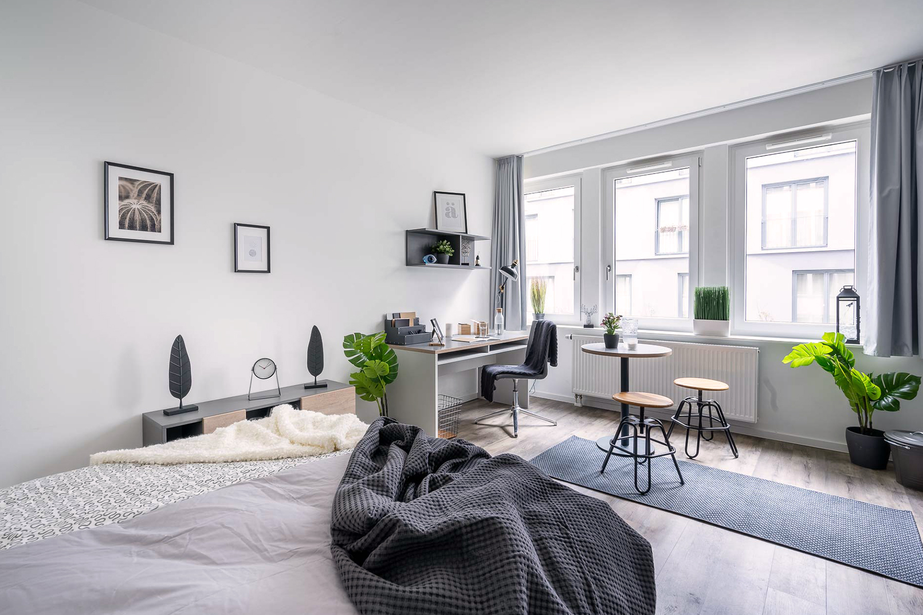 A large, light studio apartment with a double bed in the front, a round coffee table and two stools in the back beneath the window front and a desk and chair beside it.