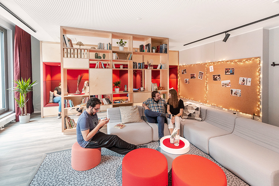 The community lobby at THE FIZZ Freiburg Mitte with cozy sitting area and a stylish bookshelf.