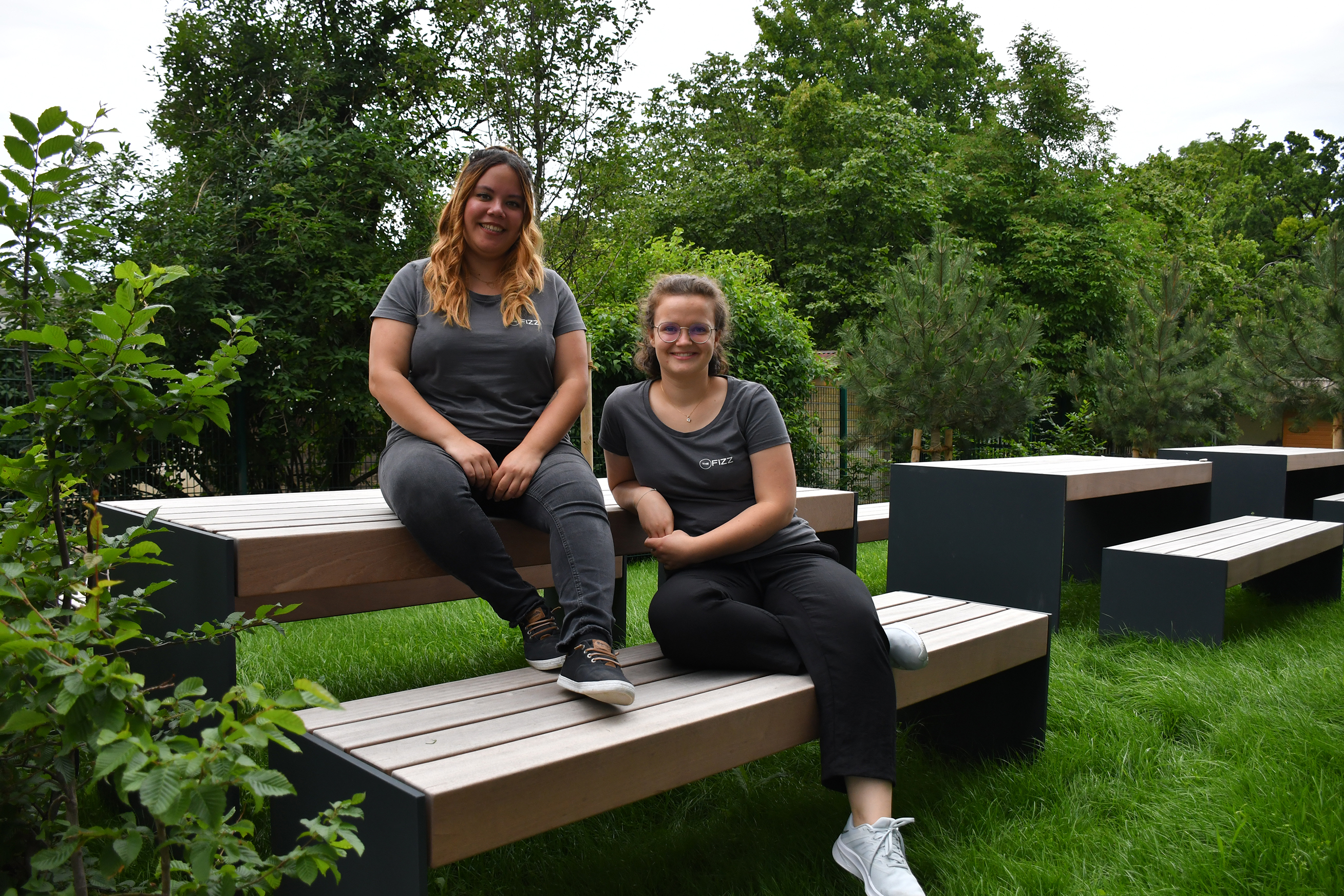 Two girls sitting casually on a bench outside, surrounded by trees. They weat dark grey T-shirts, pants and sneakers and look directly into the camera, smiling.