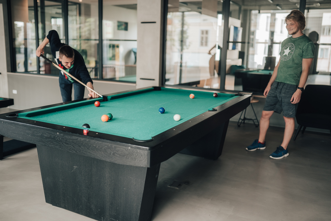 A person bends over a green billiard table, measuring their next tee. another person stands beside, watching them.