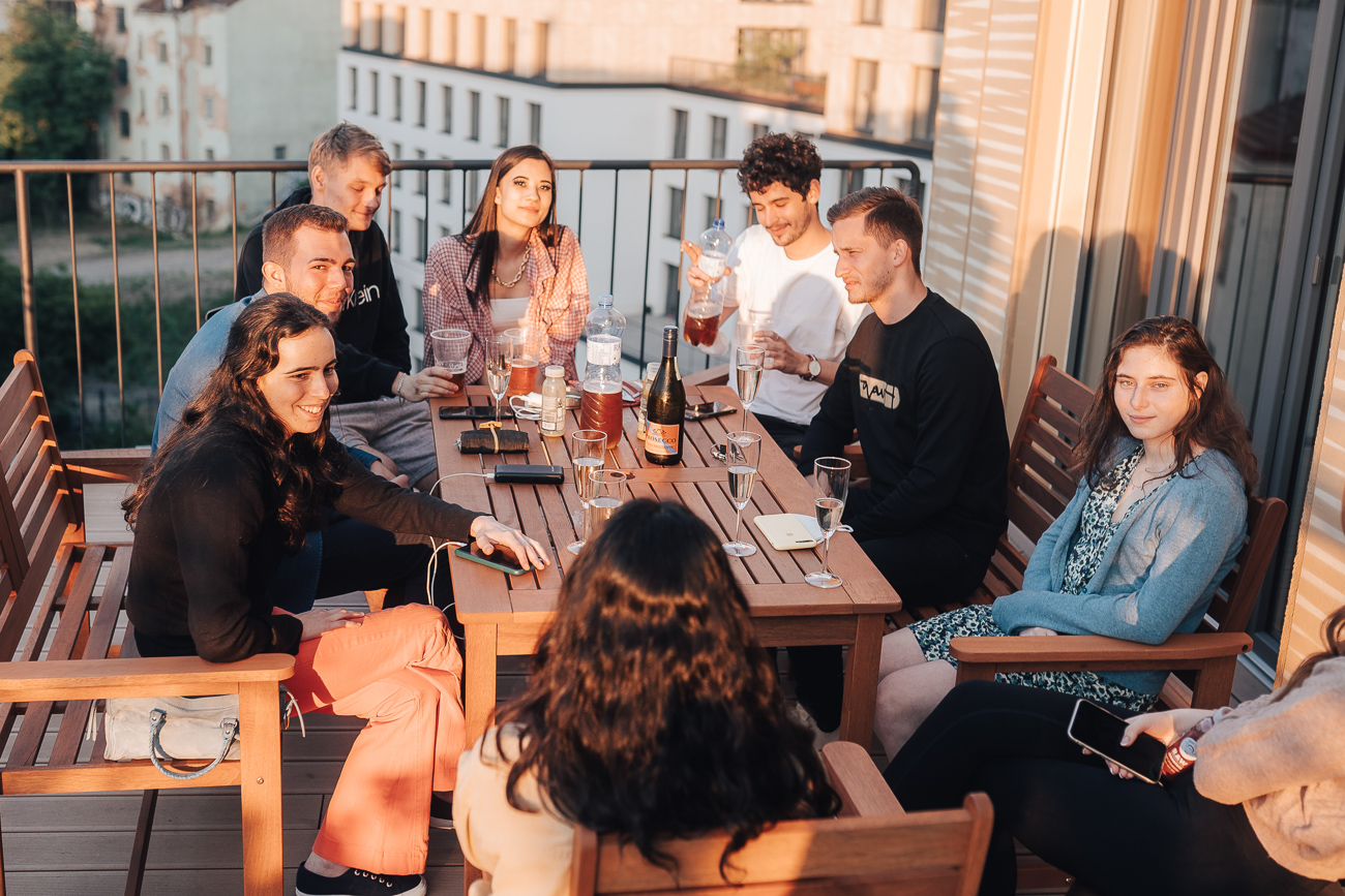 A group of students sitting outside in the sunset at a wooden table, drinking and chatting.