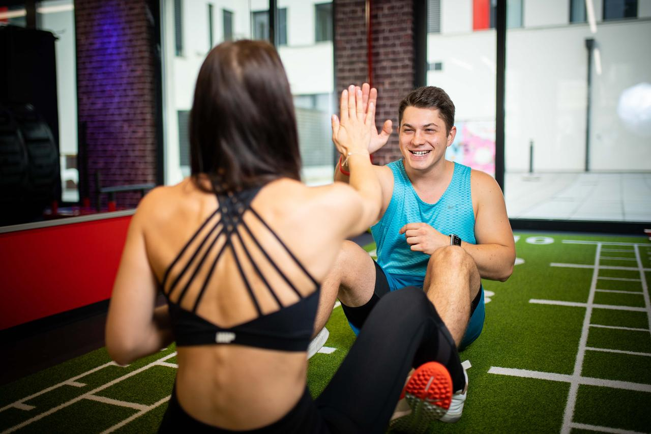 A girl and a boy are high-fiving while doing a sit-up. They both wear sport clothes. The girl sits with her back to the camera, while the boy is facing towards the camera, looking at her, smiling.