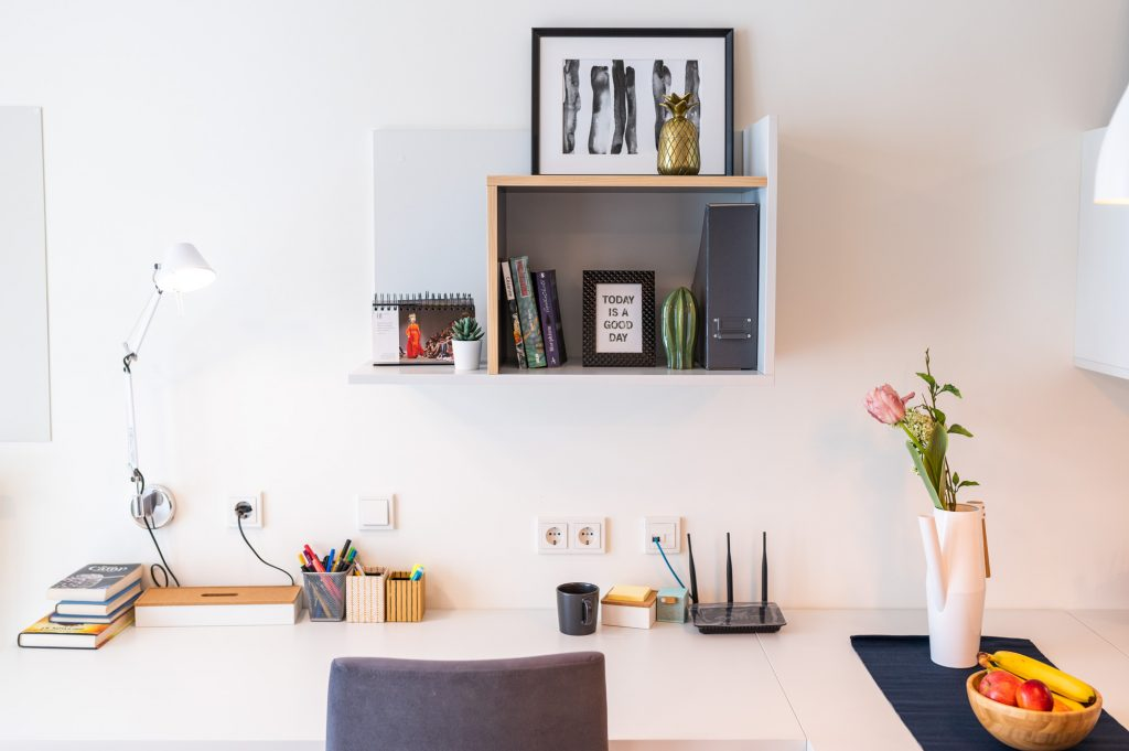 A tidy desk with lamp, a pile of books, pens in a container, coffe mug, wifi router, flowers in a vase and fresh fruits in a wooden bowl. above the table there is a shelf with books and picture frames.