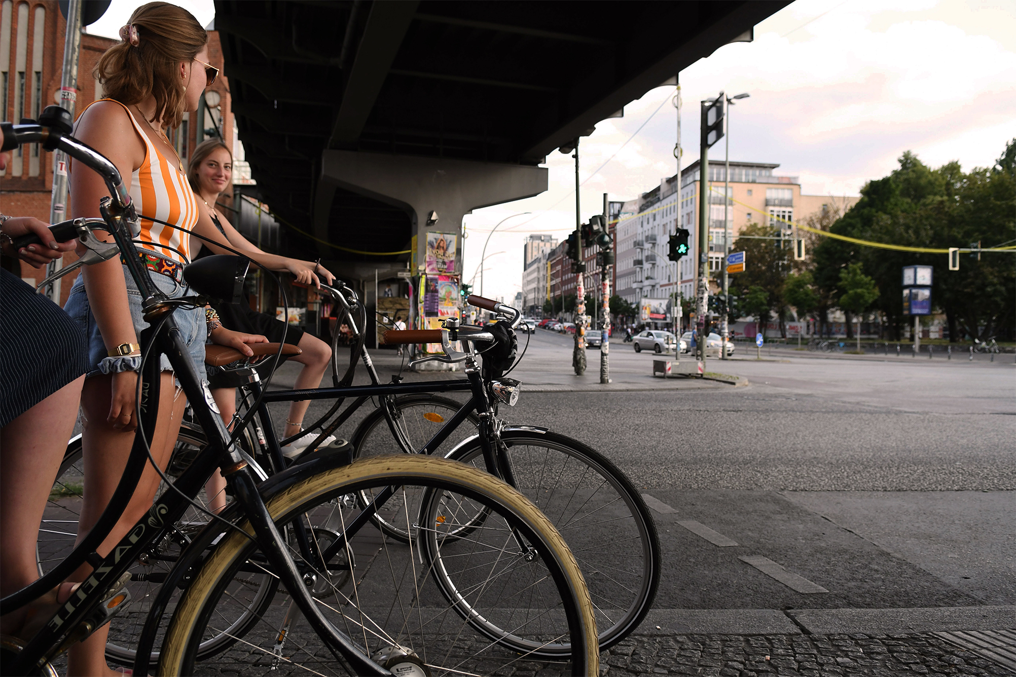A group of cyclists stand on the side of the road under an underground bridge in Berlin.