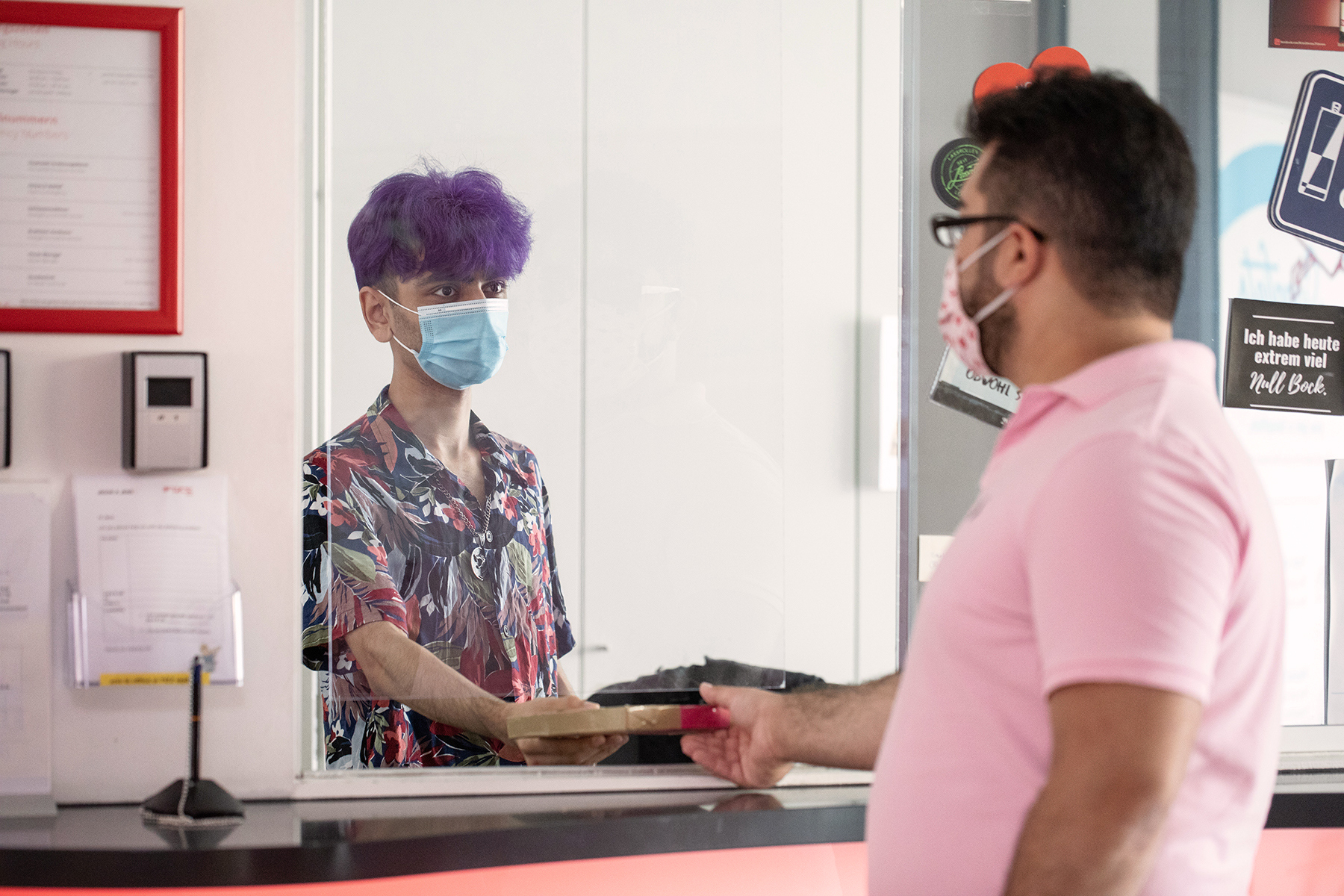 A person with purple hair and a colourful shirt hands a small parcel to another person with pink shirt, dark hair and glasses through a hole in a glass screen. They both wear surgical masks.