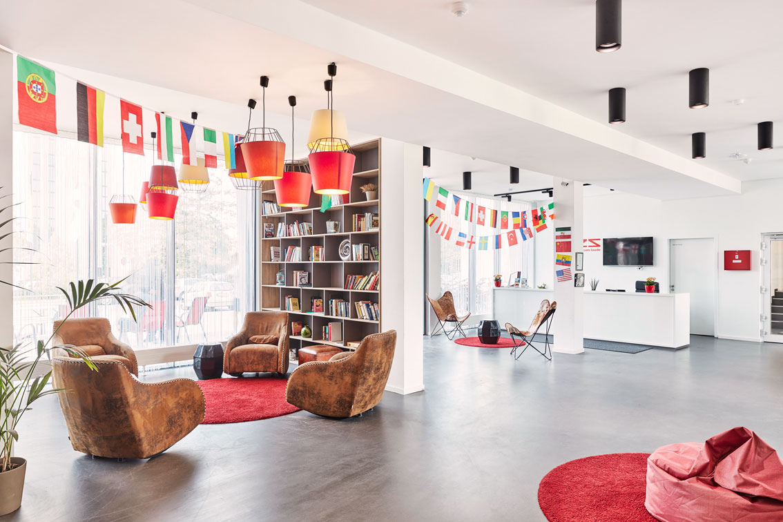 View of THE FIZZ Darmstadt Lobby with colourful lamps hanging from white ceilings, a group of cozy brown armchairs and the reception in the far back.