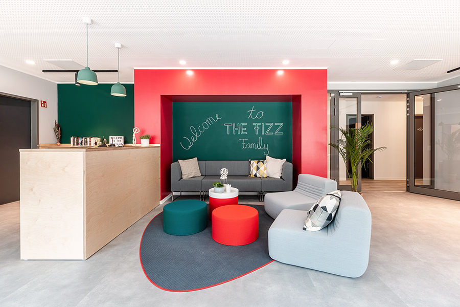 The lobby of THE FIZZ Freiburg Mitte welcomes new tenants with cozy chairs and a reception.